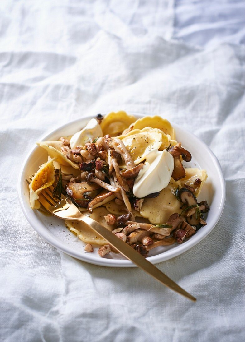 Pumpkin pansoti with butter mushrooms, rosemary and pecan nuts