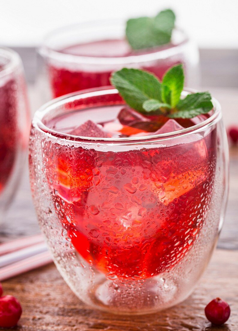 Cranberry cocktail with mint garnish on a wooden table