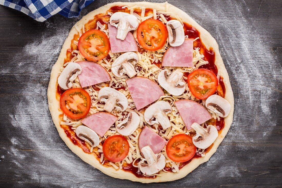 Pizza zubereiten: Pizza mit Schinken, Tomaten und Pilzen belegen