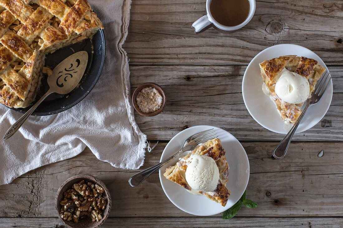 Two slices of a caramel apple pie (topped with vanilla ice cream)