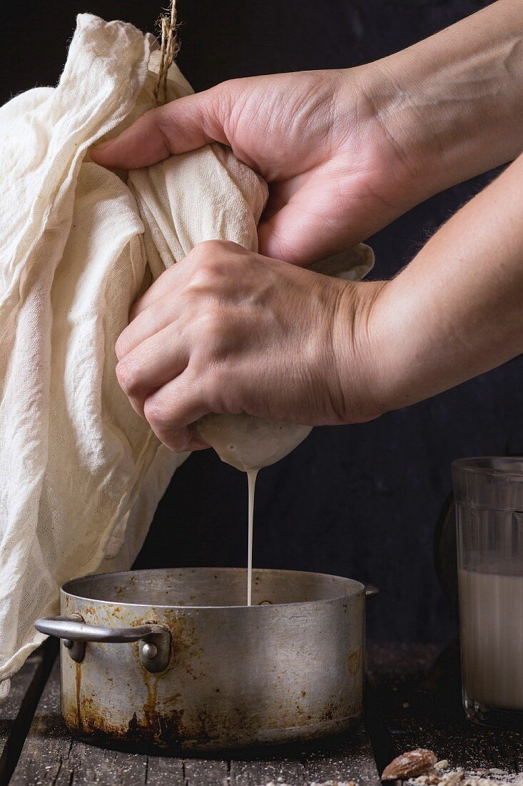Process of making non-dairy almond milk - woman s hands extracting milk from grain almond