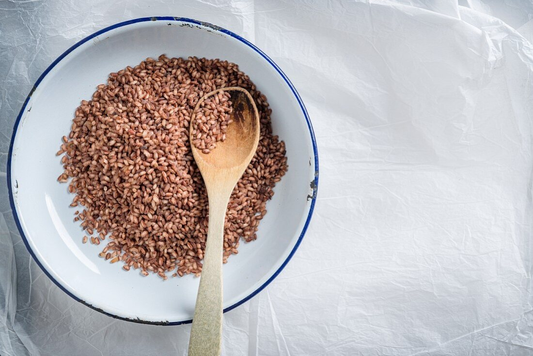 Brown rice with a wooden spoon in an enamel dish