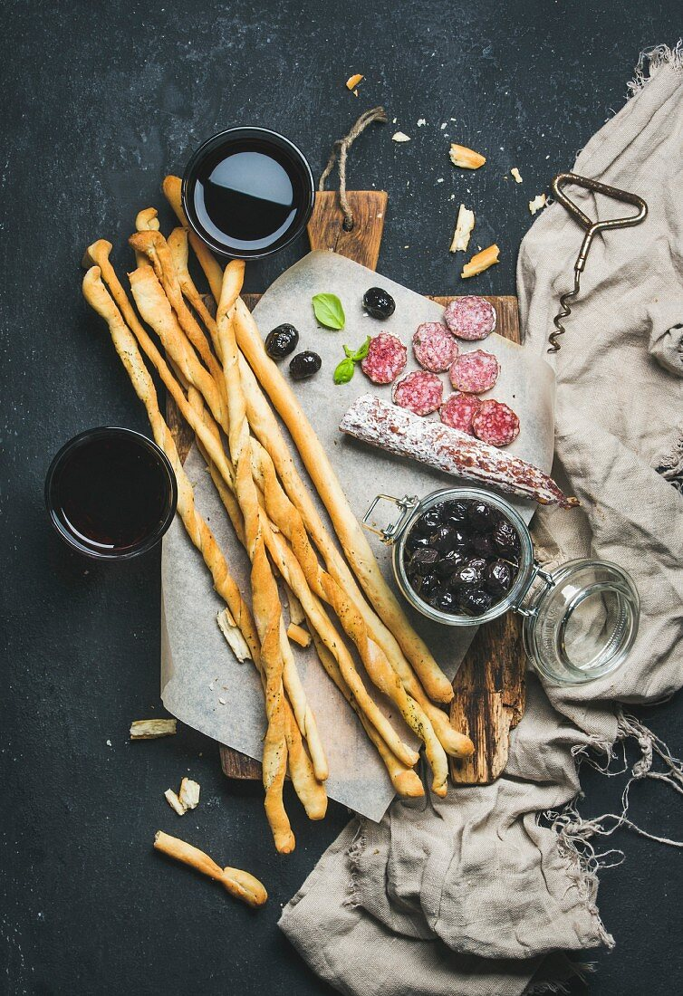 Italian Grissini bread sticks, dry cured pork meat sausage, black olives and red wine in glasses
