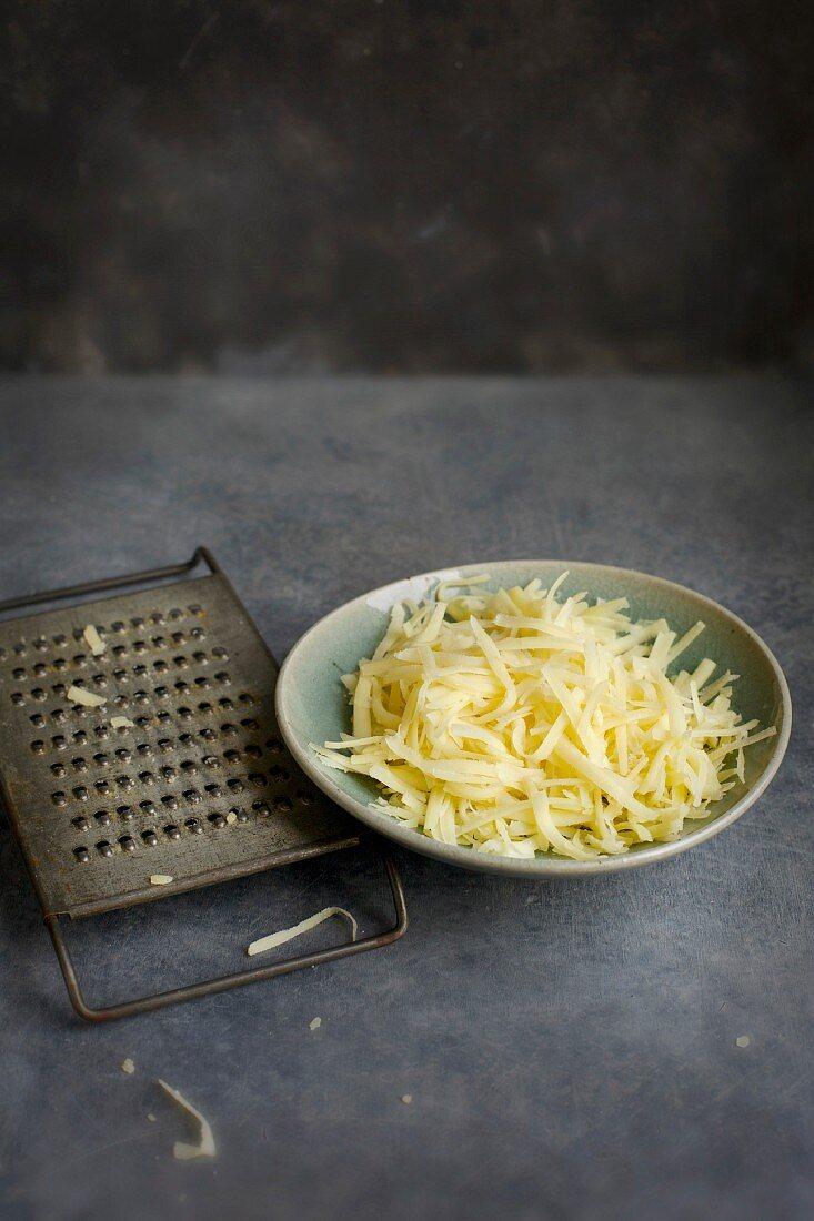 Geriebener Käse in Schüssel, daneben Vintage-Käsereibe