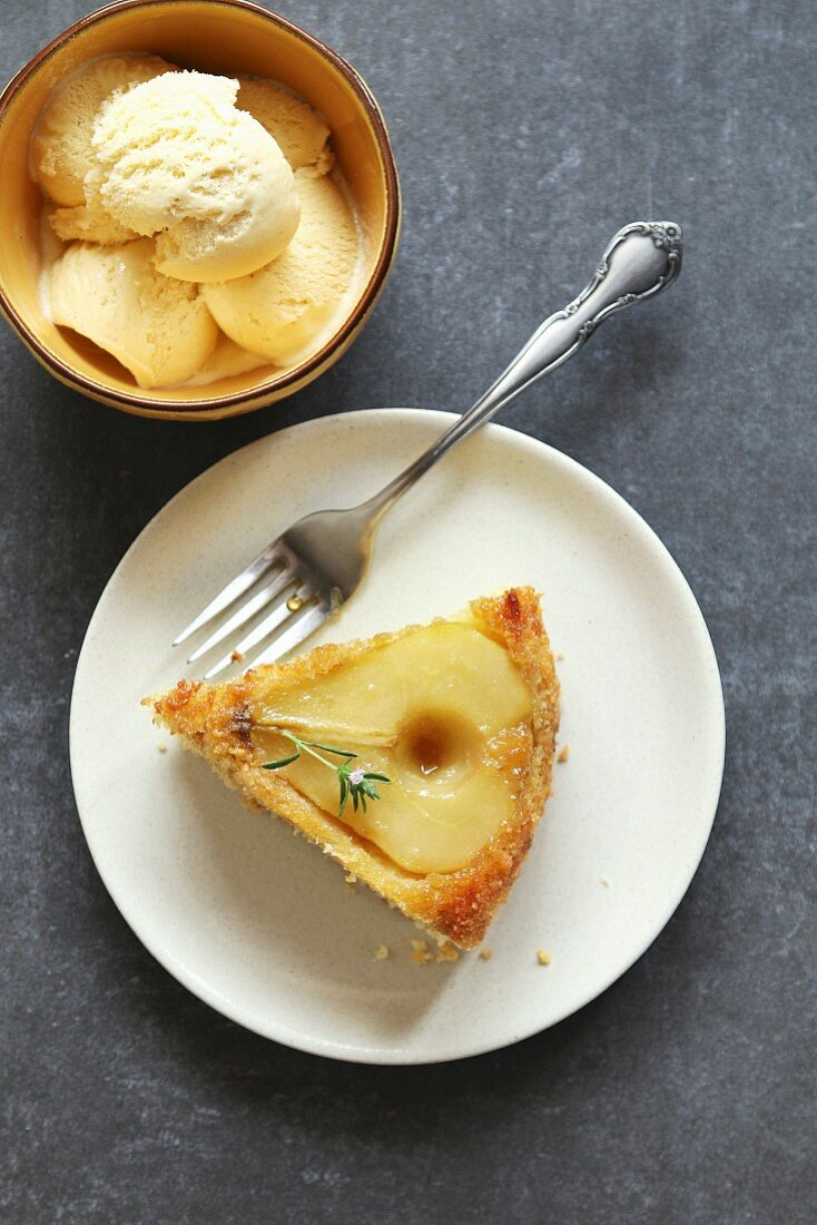 A slice of pear cake on a plate and ice cream in a bowl