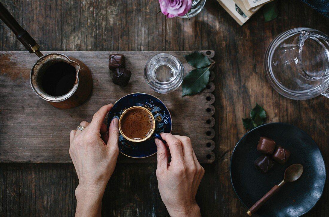 Hände halten Tasse türkischen Kaffee serviert mit Wasser und Schokolade (Aufsicht)