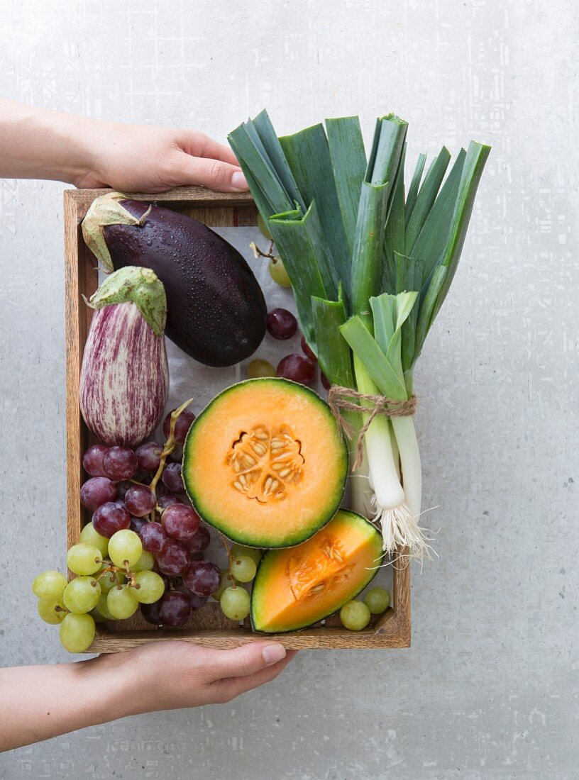 Hands holding a wooden box of fresh fruit and vegetables