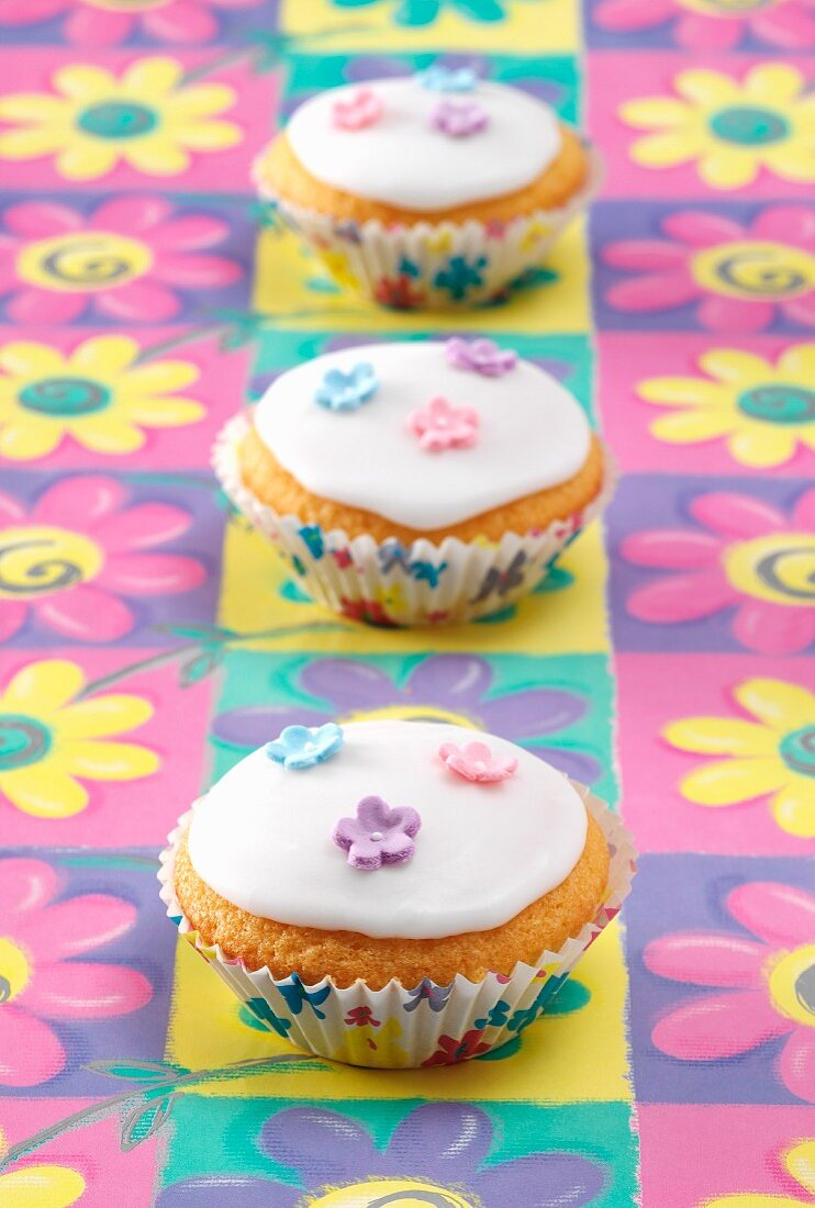 Three Fairy cakes sitting on a coloured flower pattern background