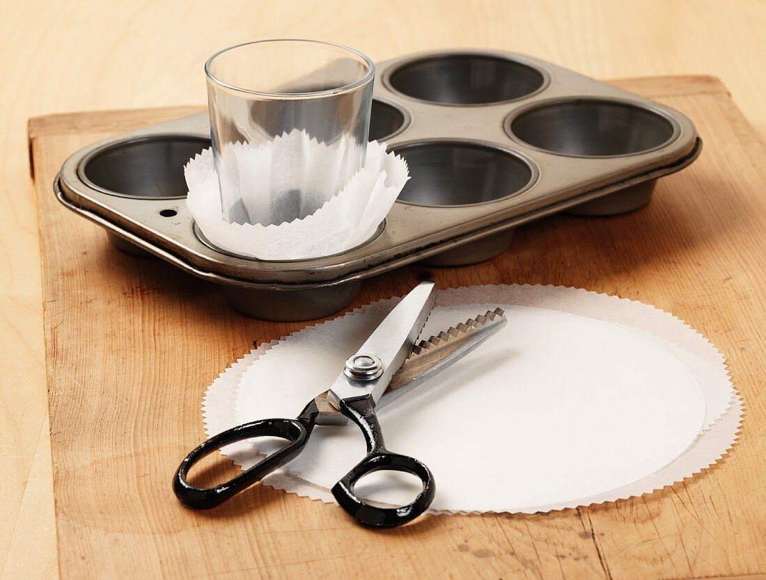 Showing how to make homemade cupcake cases using baking parchment and pinking shears