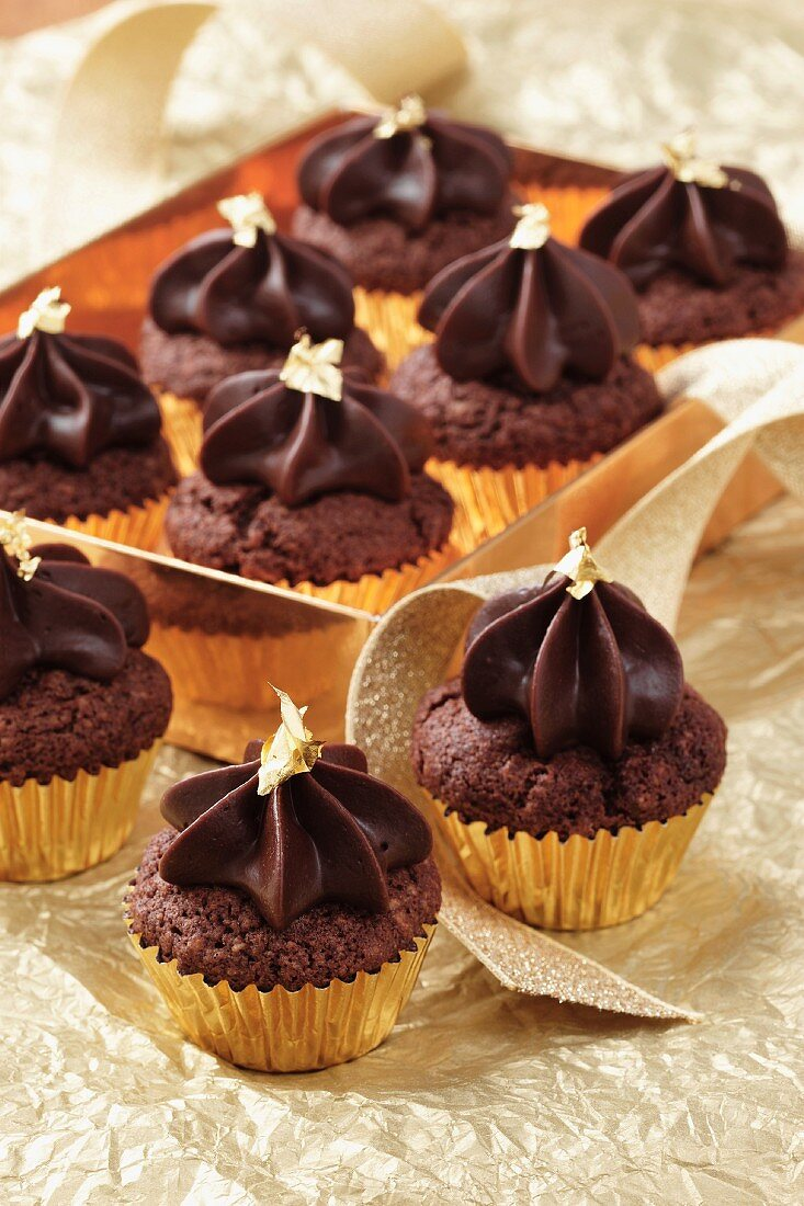 Mini chocolate cupcakes with gold leaf in gold coloured cupcake cases in a gold box all on a gold coloured background