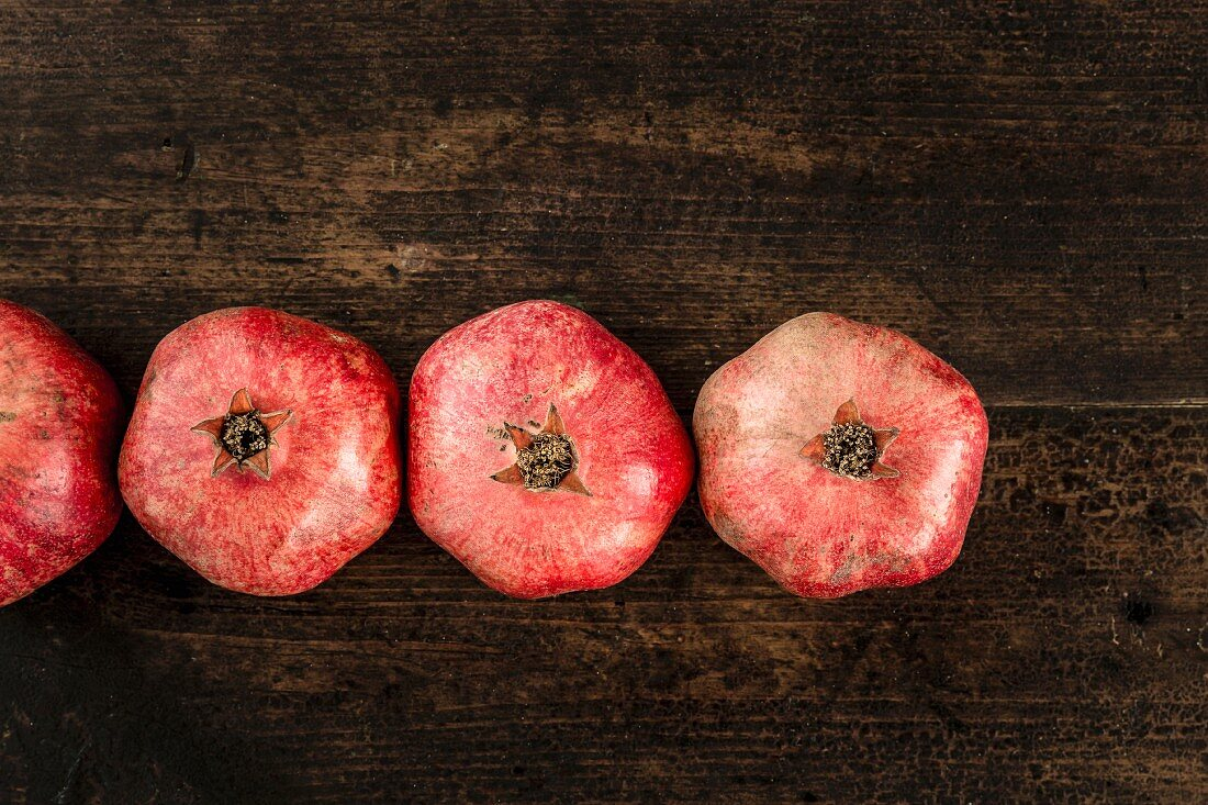 Row of pomegranates on a wooden surface