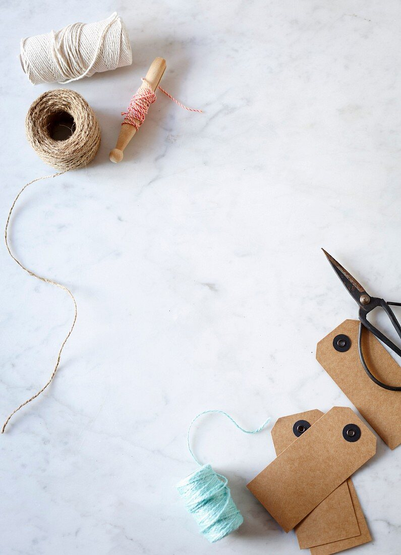 Reels of yarn and twine, cardboard labels and scissors on marble table