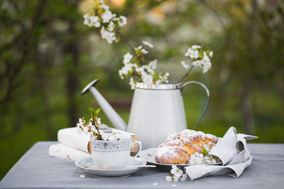 Coffee cup, books, plaited bun, and flowers in watering can on grey tablecloth
