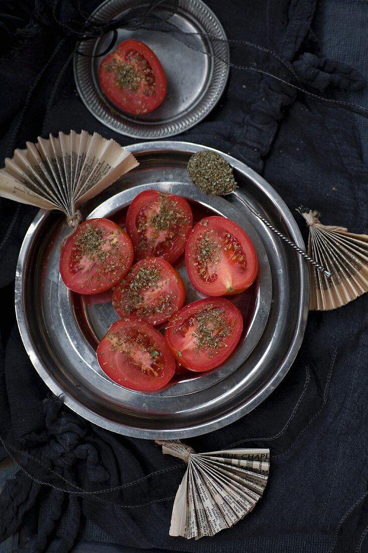 Tomatoes with dried oregano on metal plates