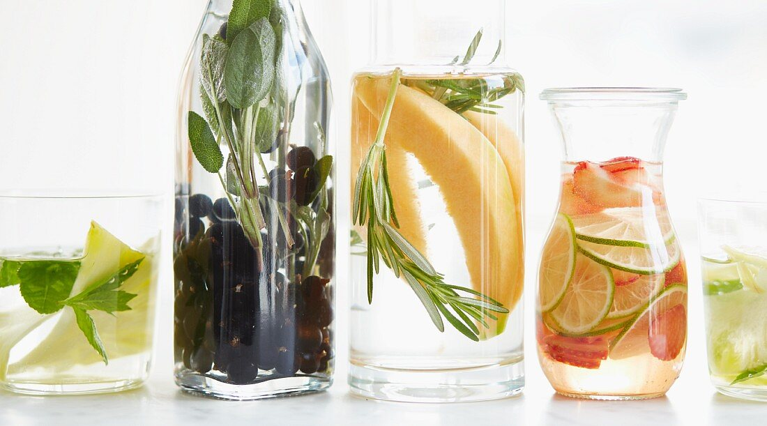 Various flavoured waters in glasses and jugs