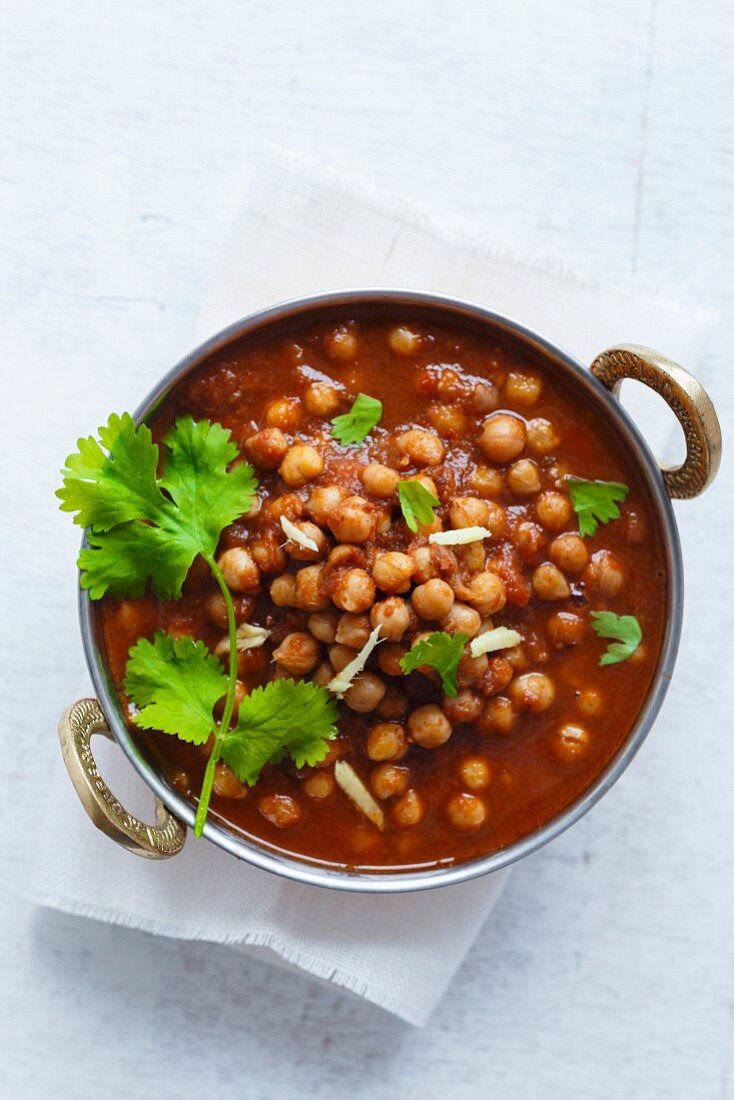 Chickpeas soaking in a bed of onion tomato sauce, garnished with coriander leaves and ginger juliennes