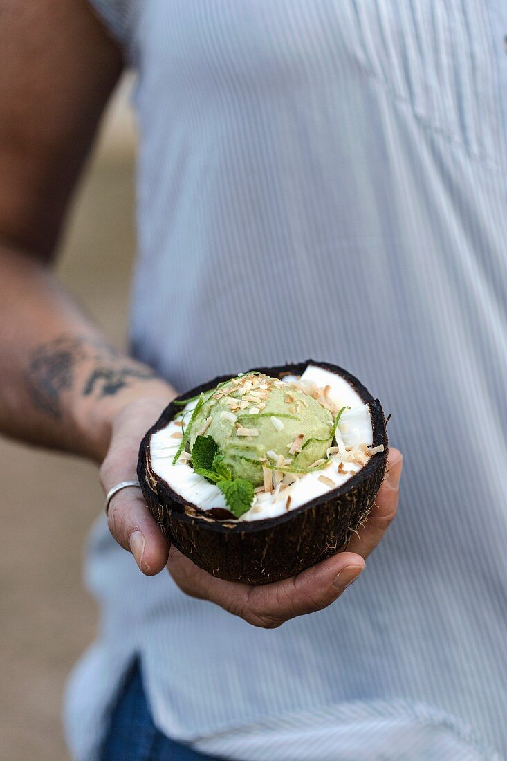 A woman is holding a coconut bowl filled with a scoop of coconut and avocado ice cream