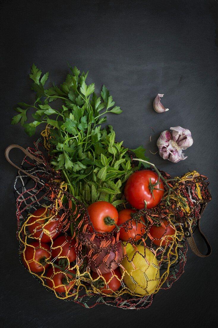 Vegetables in string bag fresh from the market on slate background