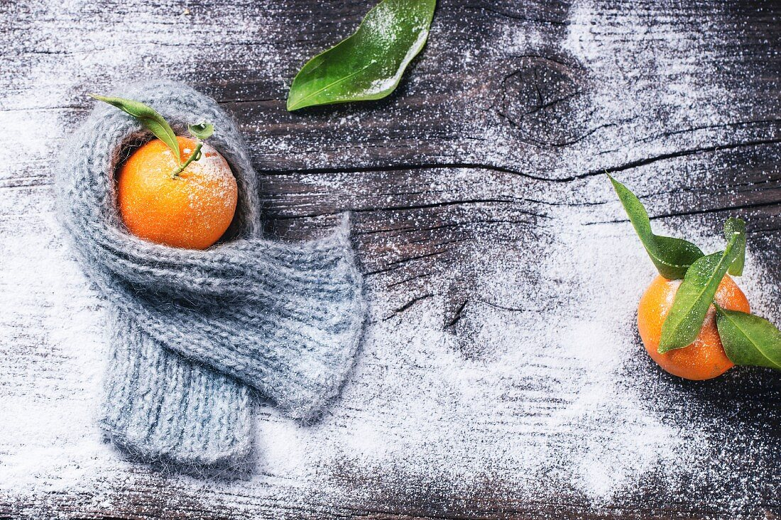Tangerine in scarf over wooden background with snow and leaf