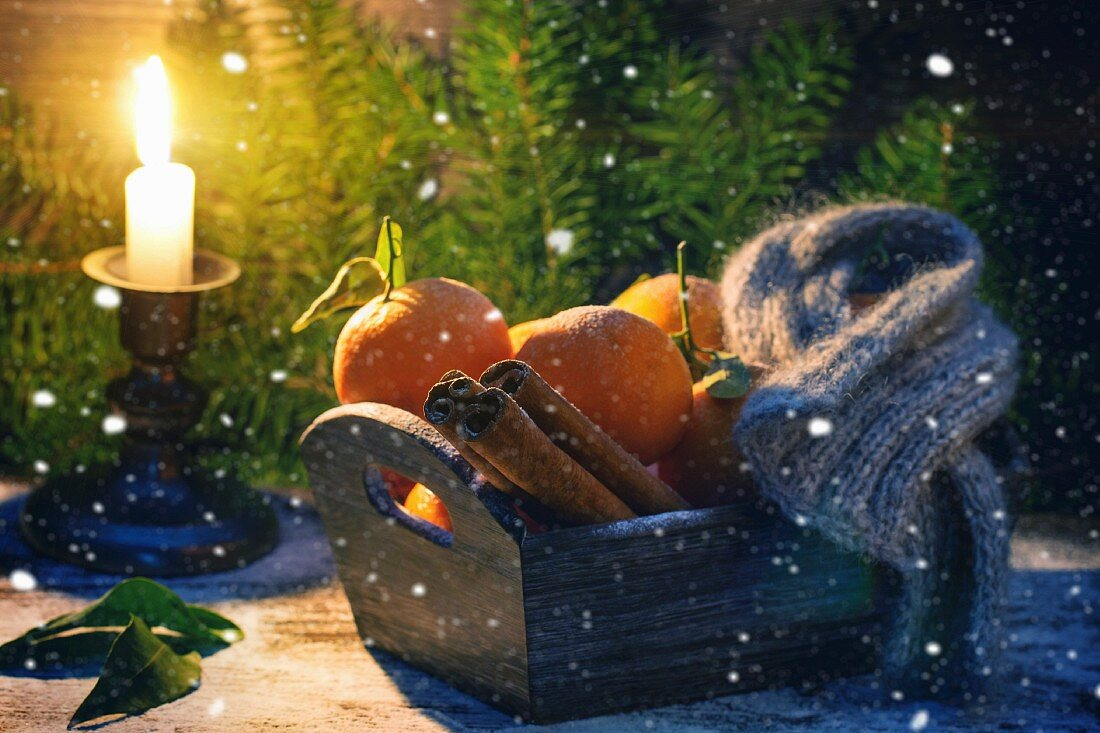 Wooden basket with tangerines, cinnamon sticks and scarf over wooden background