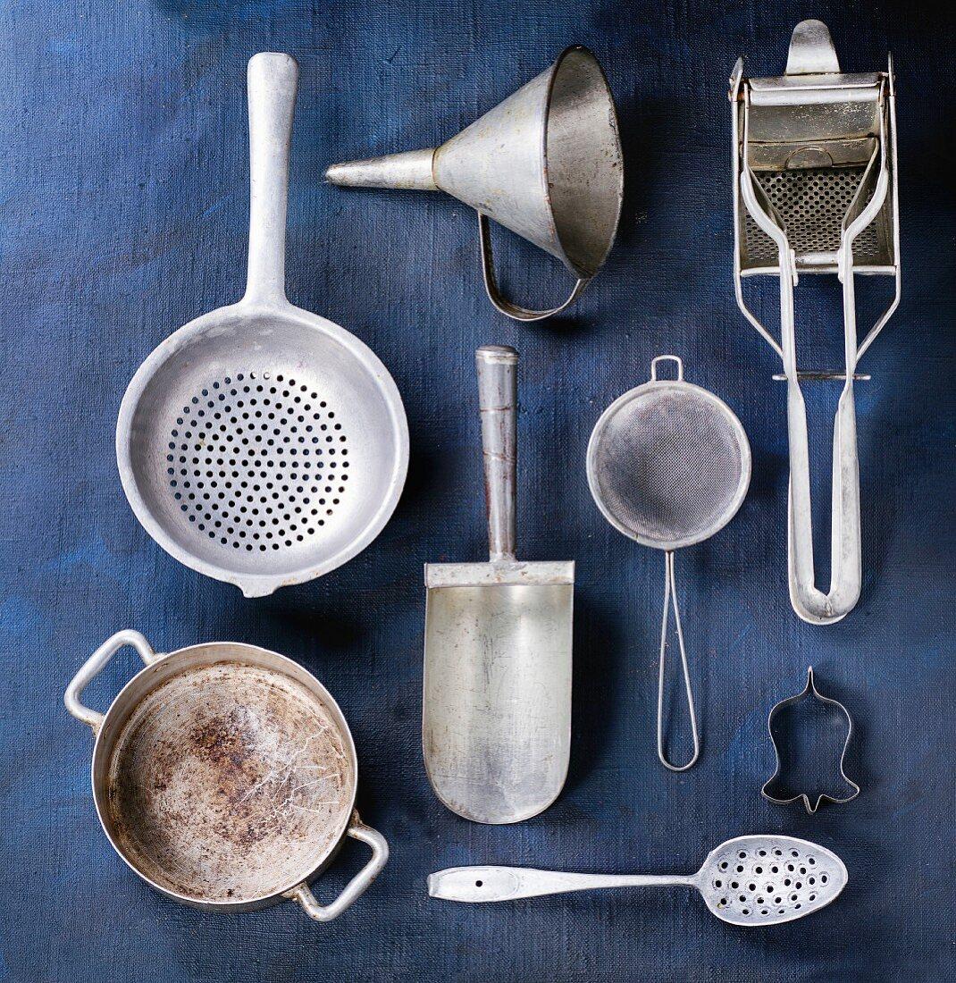 Set of vintage aluminum cookware over dark blue canvas as background