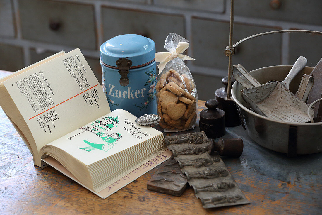 Open cookery book, biscuits and vintage kitchen utensils
