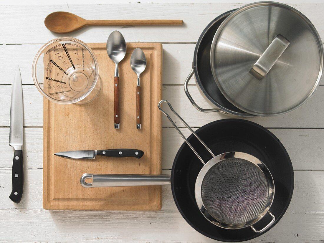 Various kitchen utensils: pot, pan, sieve, measuring cup, knife, spoons