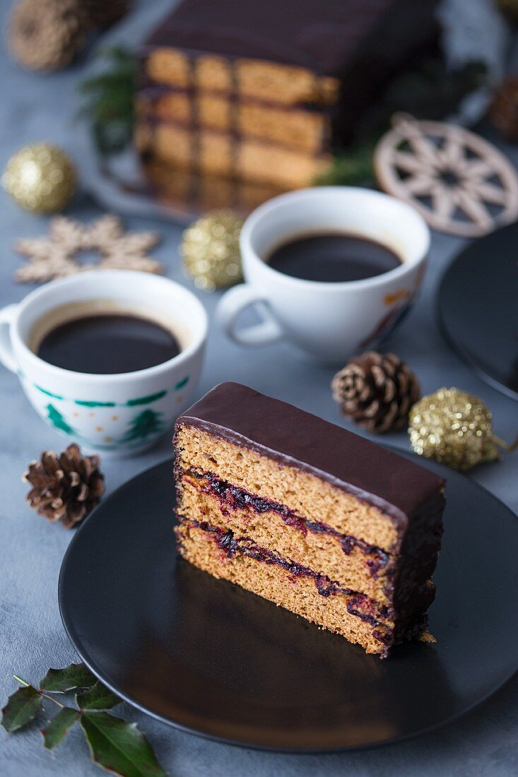 Slice of a traditional Polish gingerbread cake with plum jam and chocolate ganache