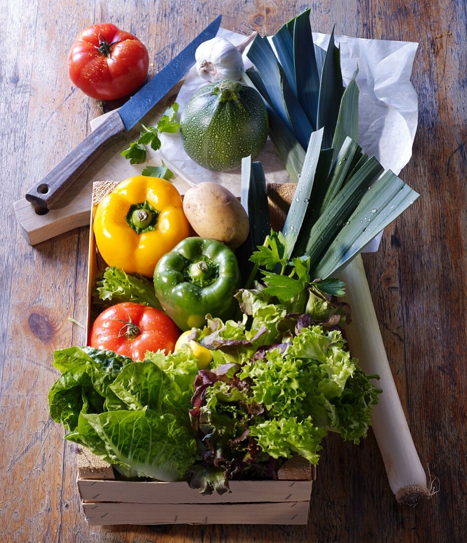 Market vegetables in a wooden box and on a wooden board with paper