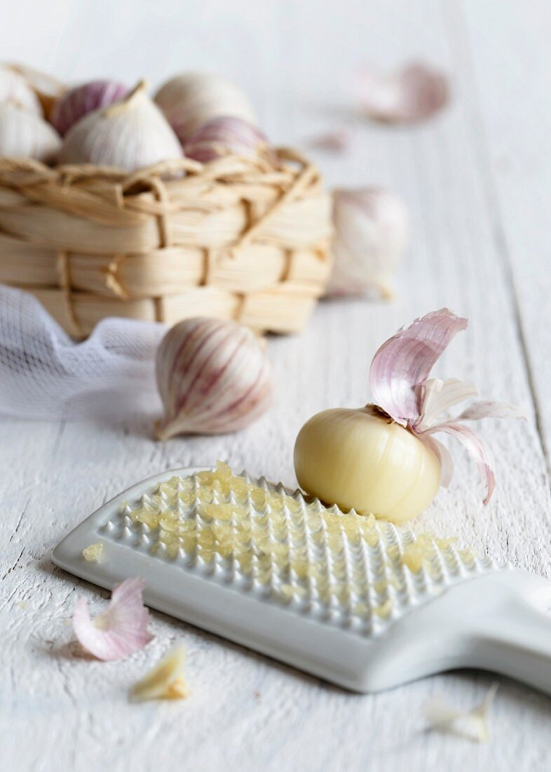 Peeled single clove garlic grated on a white ceramic grater with a straw basket full of unpeeled single clove garlics