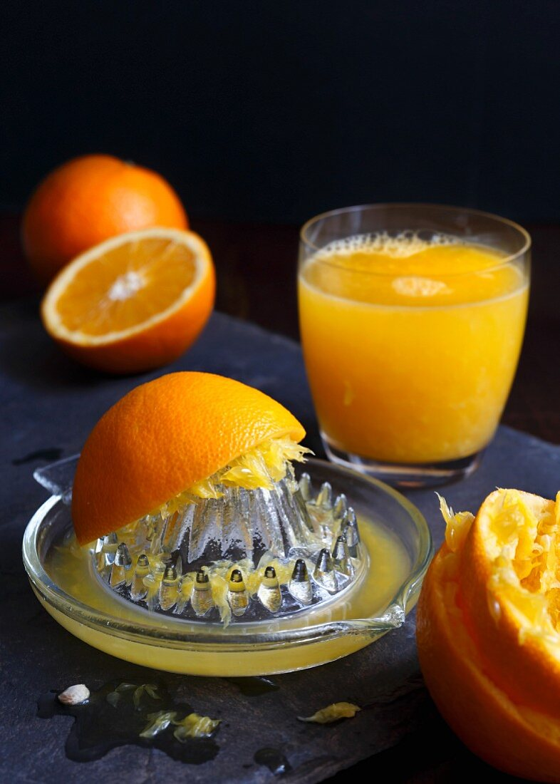 Manual glass juicet extractor with squeezed oranges and a glass of orange juice on a dark slate