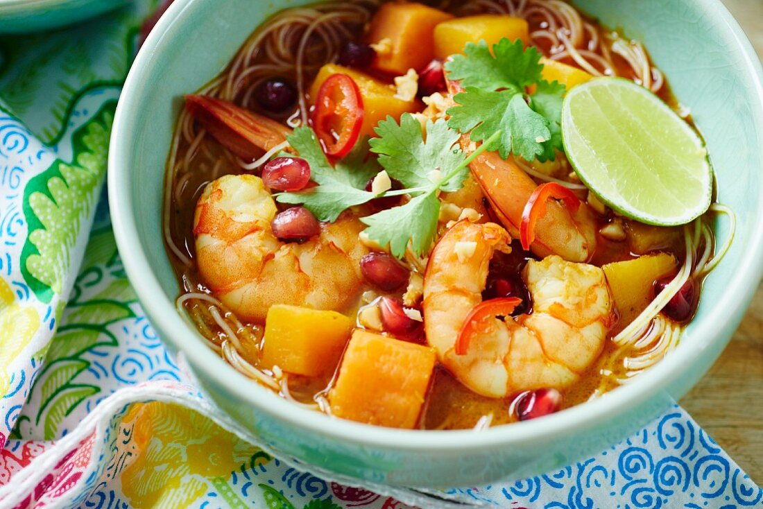 Bowl of prawn Laksa soup with toppings of pomegranate and coriander
