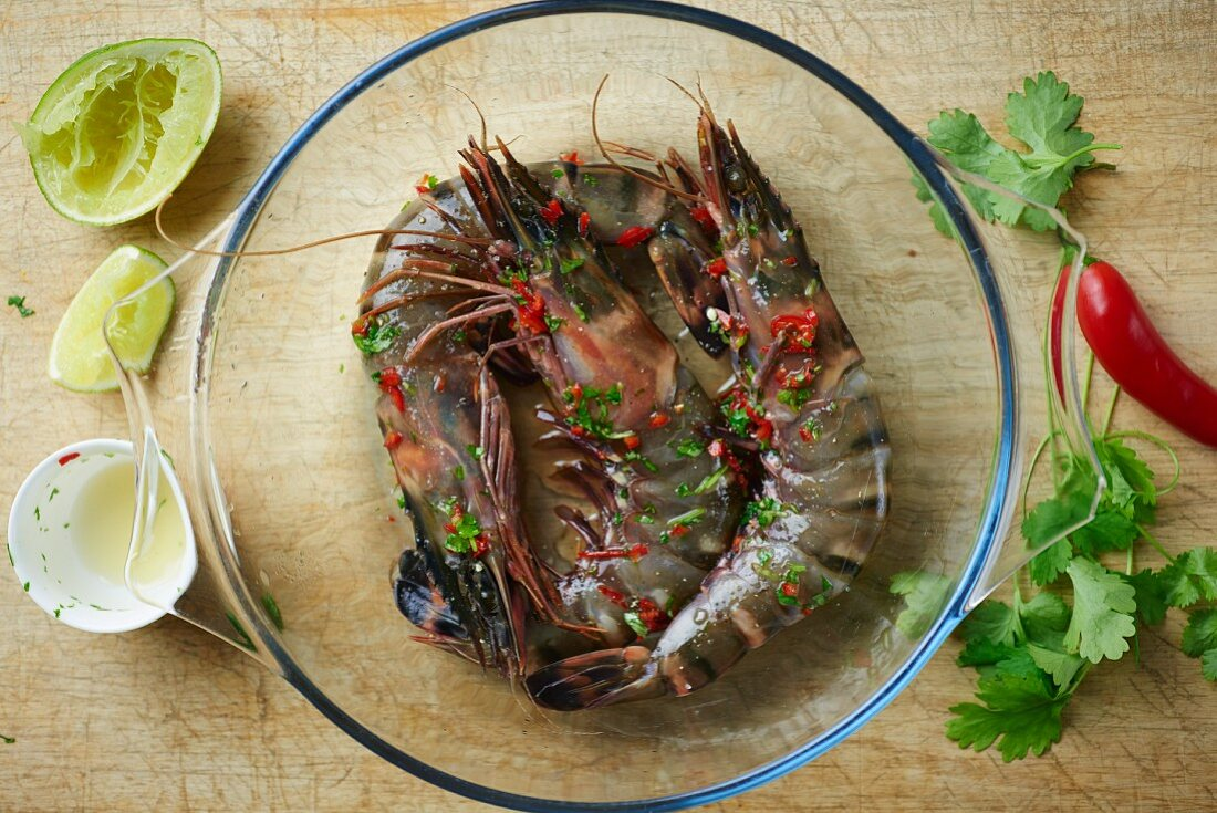 Raw tiger prawns being marinated in lime, honey, chilli and coriander