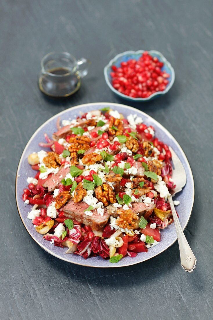 Radiccio and beetroot salad with roastbeef, pomegranate and caramelized walnuts