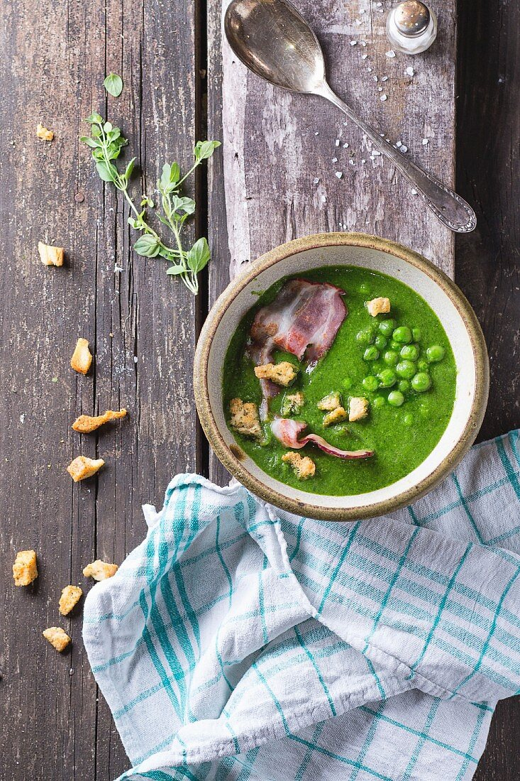 Cream soup of green peas in ceramic bowl with fried bacon and croutons