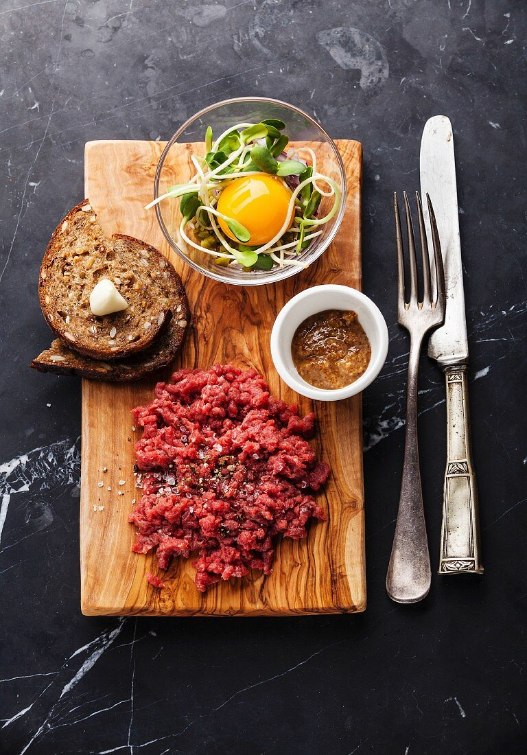 Beef tartare steak with salad and garlic toasts on dark marble background