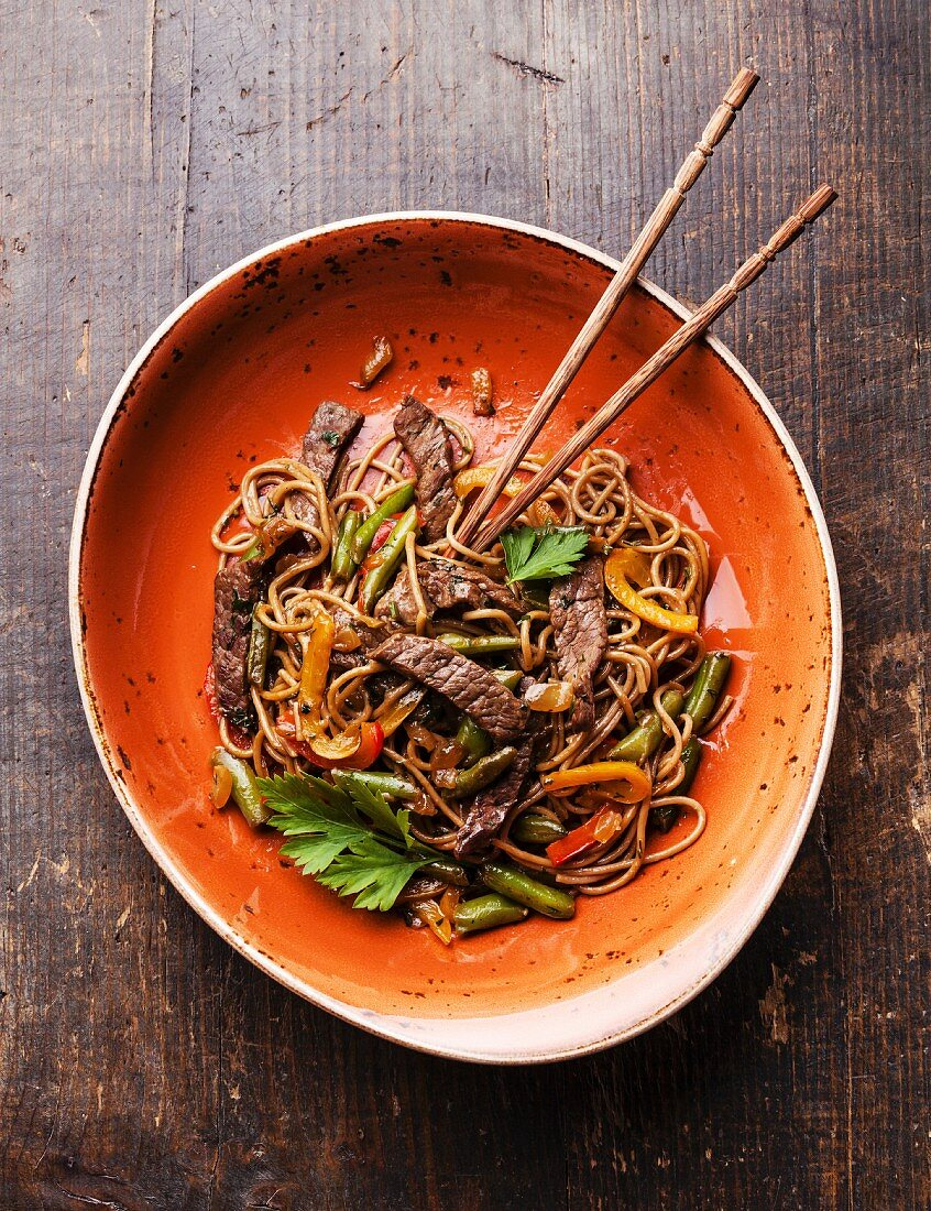 Fried noodles Yakisoba with beef on red plate