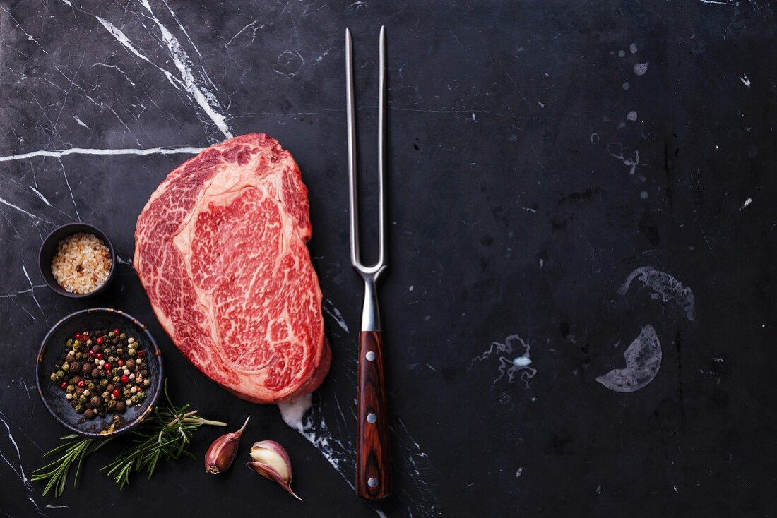 Raw fresh marbled meat Black Angus Steak Ribeye, seasonings and meat fork on dark marble background