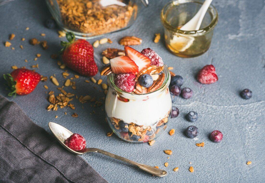 Yogurt oat granola with fresh berries, nuts, honey and mint leaves in glass jar