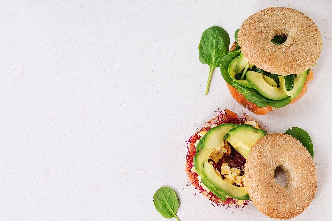 Two Bagels with salted salmon, spinach, beet sprouts, avocado and scrambled egg over white stone surface