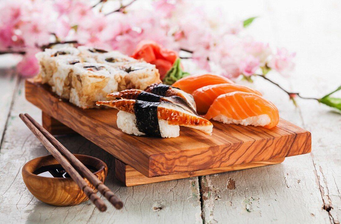 Sushi Set with sashimi and sushi rolls on olive wood board on blue wooden background