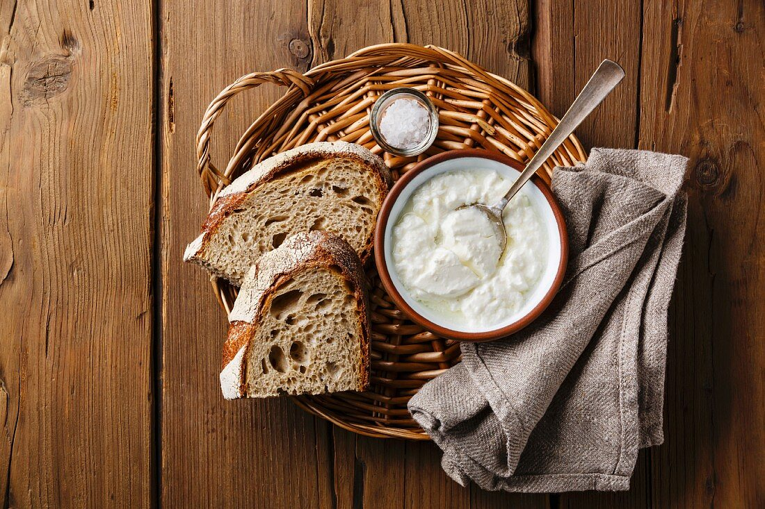 Clabber sour milk and brown rye bread on wicker tray on wooden background