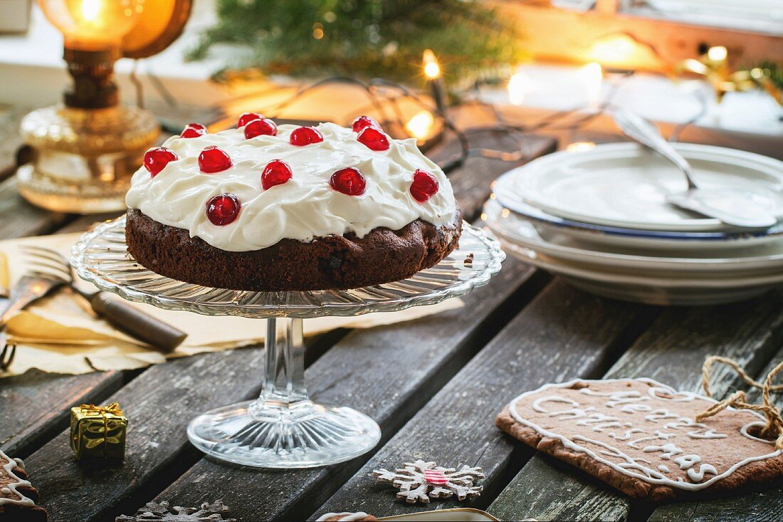 Christmas table setting with chocolate cherry cake and sugar cookies