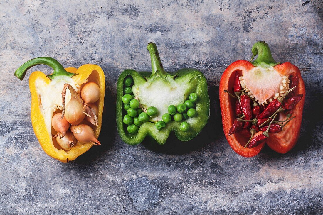 Half of raw red, green and yellow peppers stuffed by little onions, peas and red hot chili peppers