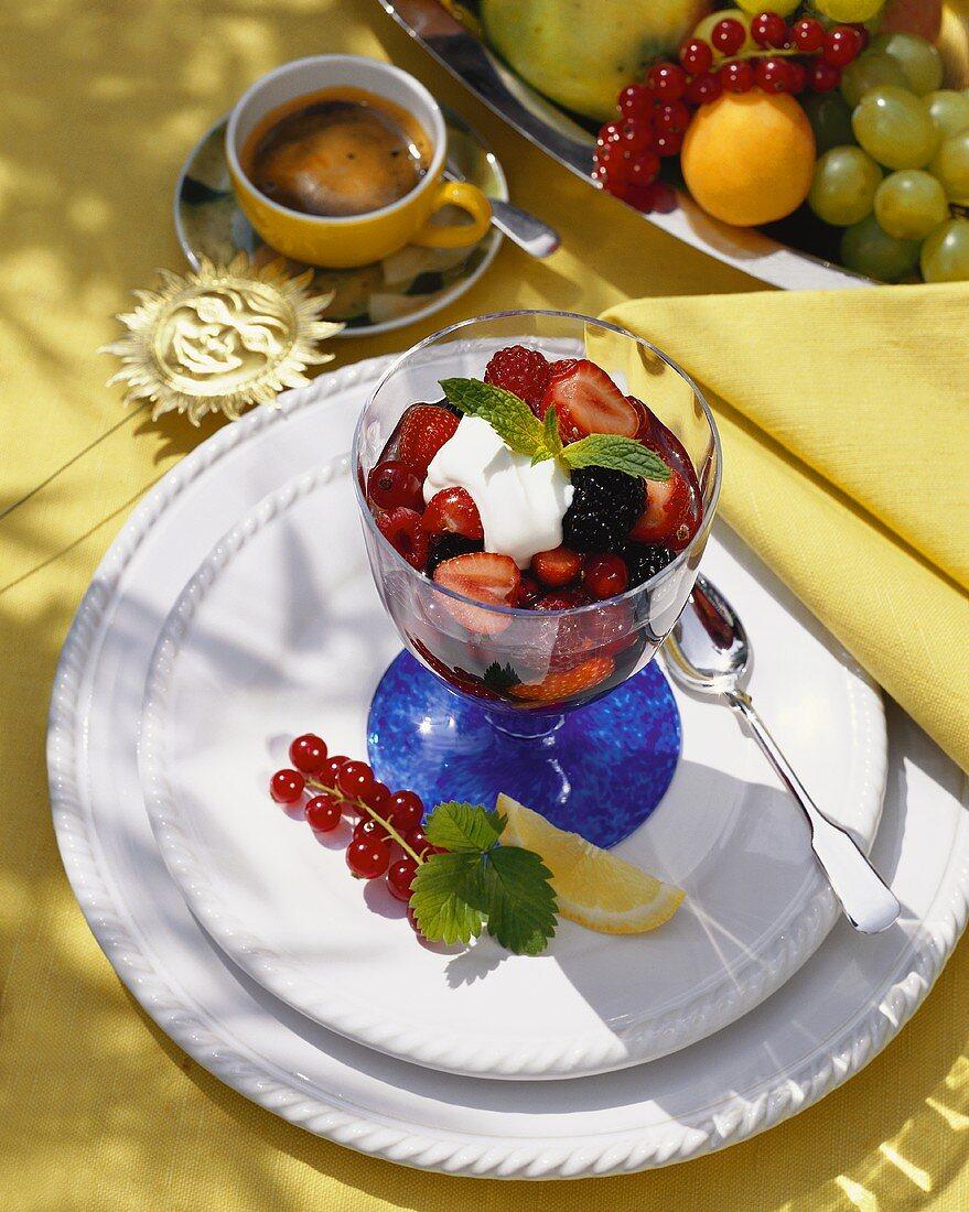 Assorted berry gelatin with cream in a dessert glass