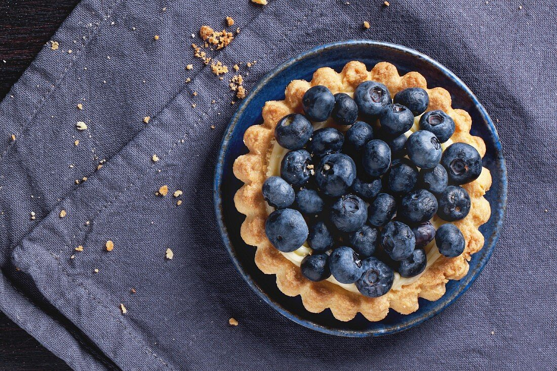 Top view on blueberry tart served on blue ceramic plate over textile napkin