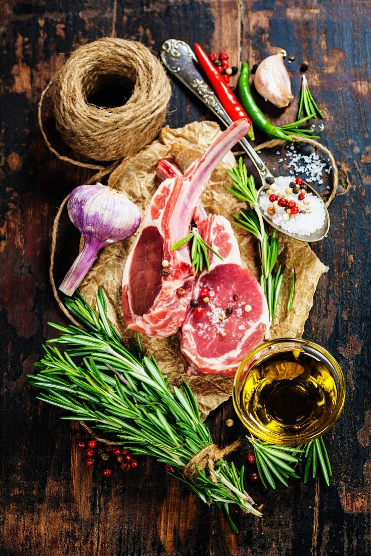 Raw lamb cutlets with vegetables, herbs and spices