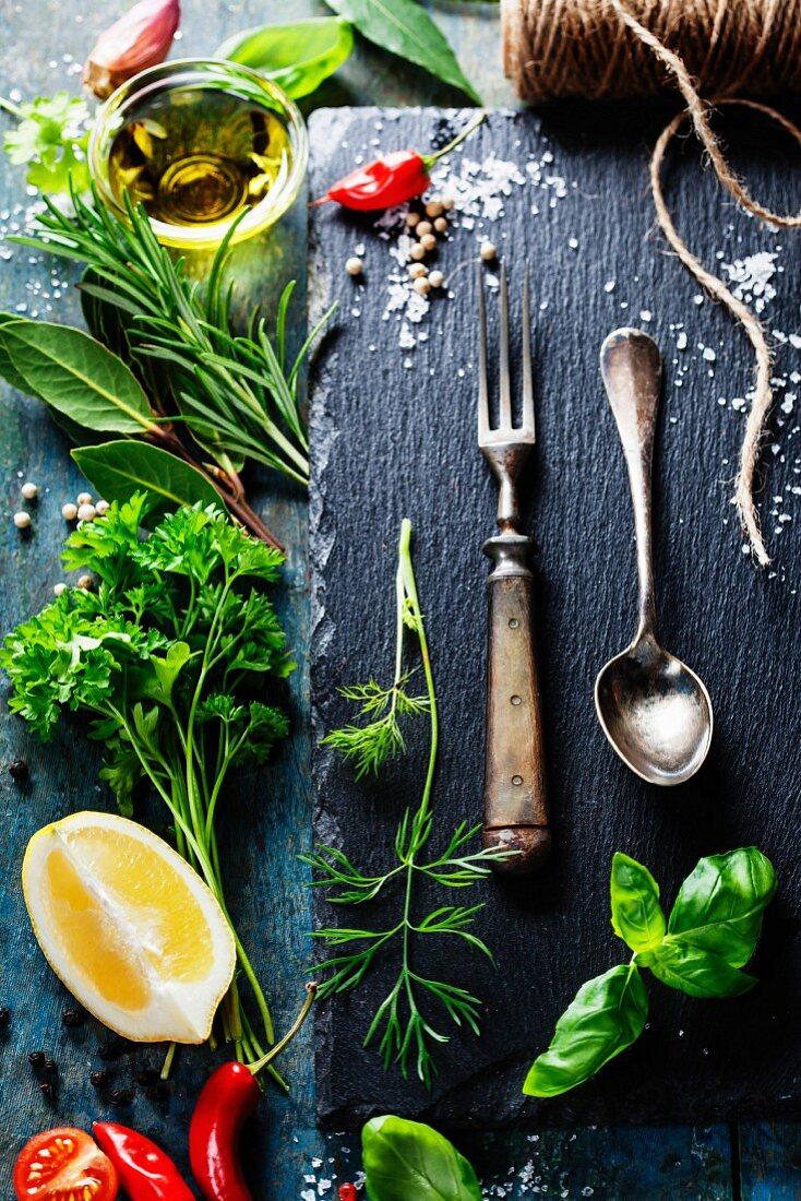 Food background, with herbs, spices, olive oil, salt, lemons and vegetables