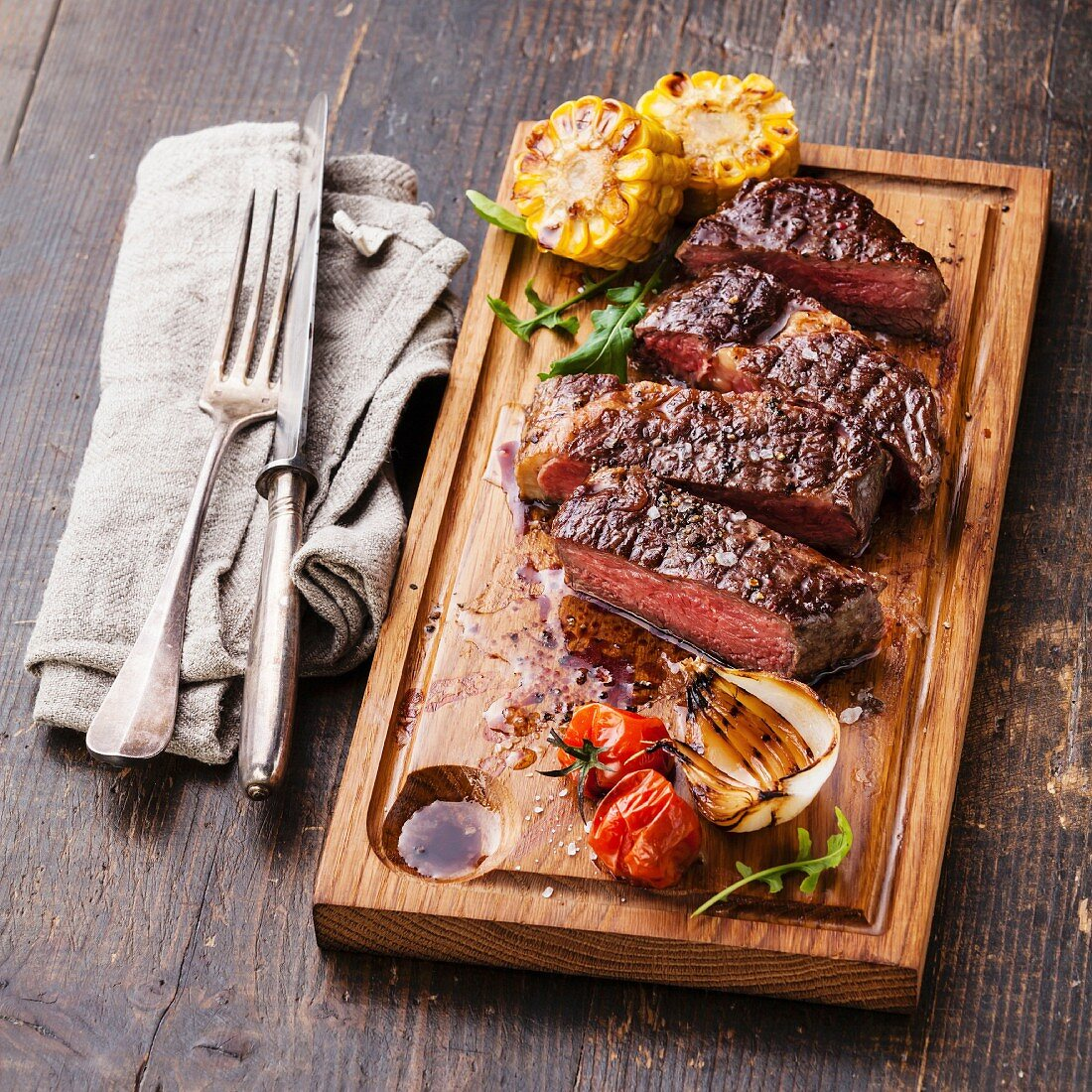 Sliced medium rare grilled Beef steak Ribeye with corn and cherry tomatoes on cutting board
