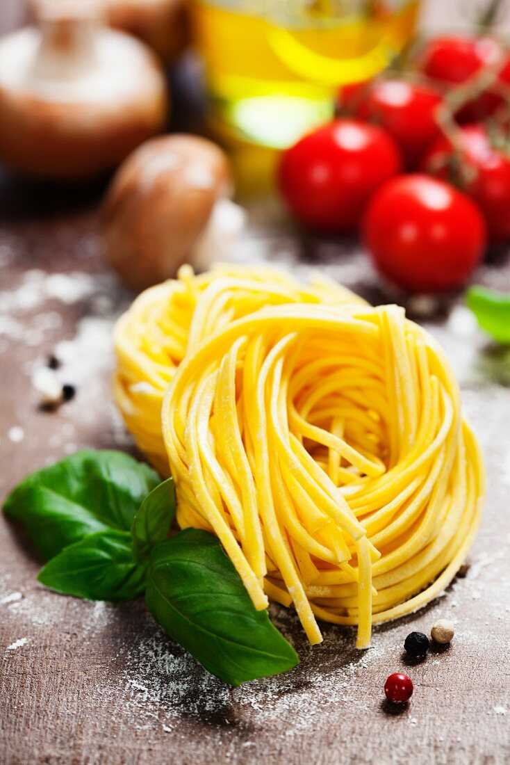 Fresh pasta and italian ingredients on wooden board